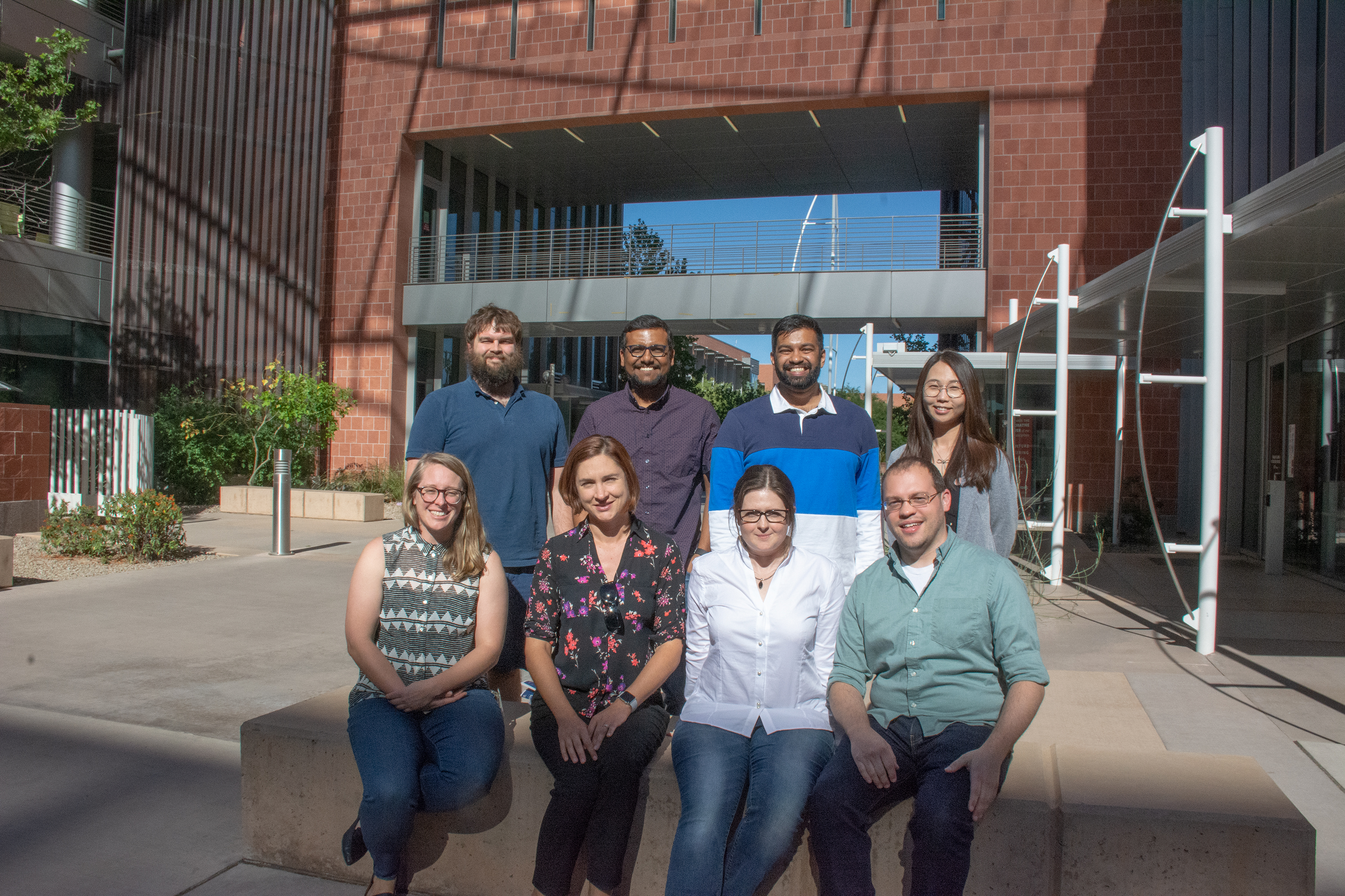 Eight postdoctoral fellows from 2019 sitting outside