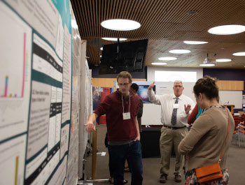 Student presenting a poster at the showcase