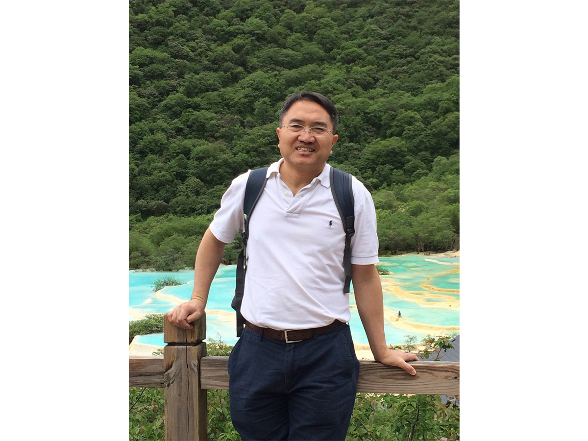 Dr. Xianchun Li wearing a white polo and blue slacks in front of thick green trees and blue-green water.