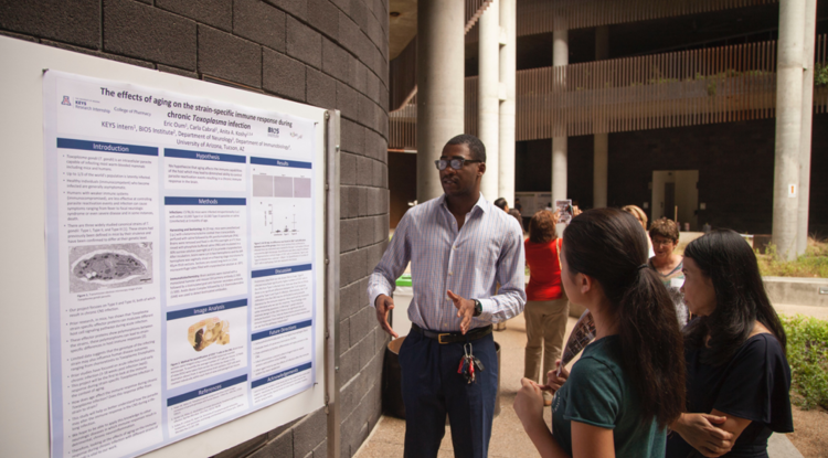 A student giving a presentation on a scientific poster