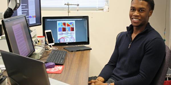 Ike Chinyere sitting at his desk, surrounded by five screens.