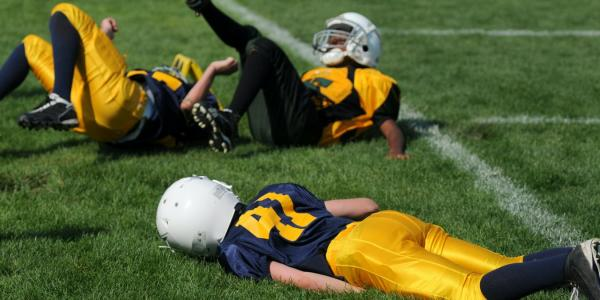 children laying on ground while playing football