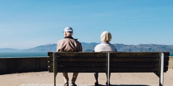 Two elderly people sitting on a bench looking over the horizon with mountains in the distance